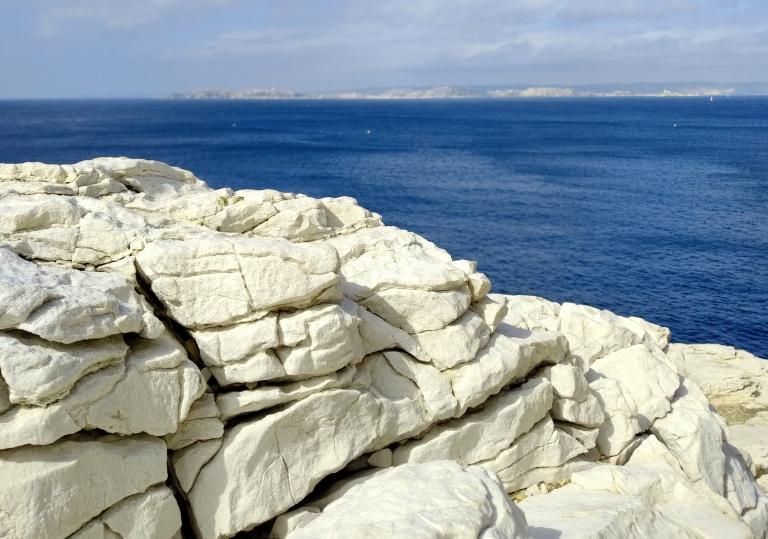 Contraste saisissant entre le bleu cobalt de la mer méditerranée et le calcaire éclatant de la calanque.